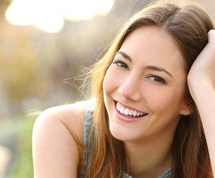 Woman with brown hair smiling outside