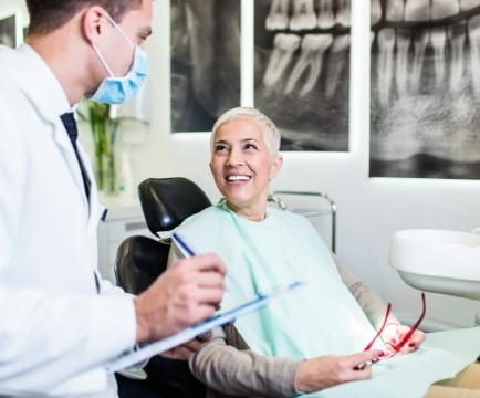 Dentist and patient discussing the cost of dental implant tooth replacement